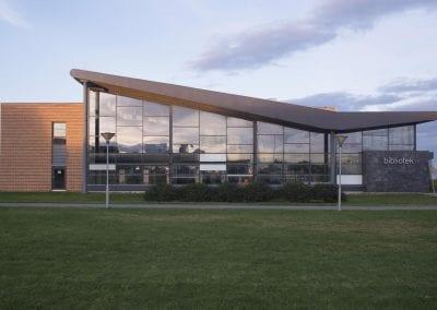 Foto av Vadsø bibliotekbygg, med moderne arkitektur og en fasade av glass, stein og tre.